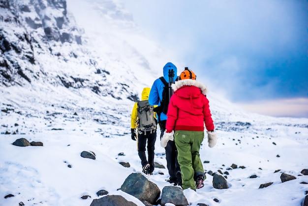 Grupa ludzi wędruje zimą