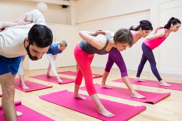 Grupa ludzi wykonujących piramidy stanowią ćwiczenia jogi