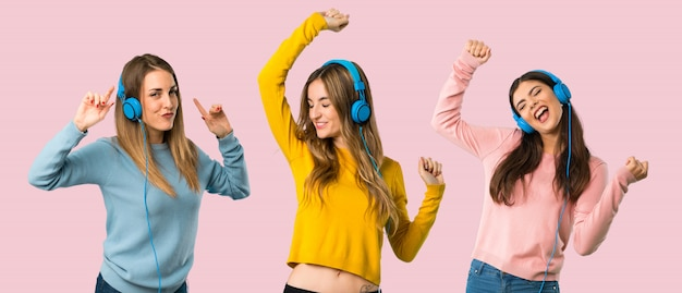 Grupa ludzi z kolorowymi ubraniami słucha muzyka z hełmofonami