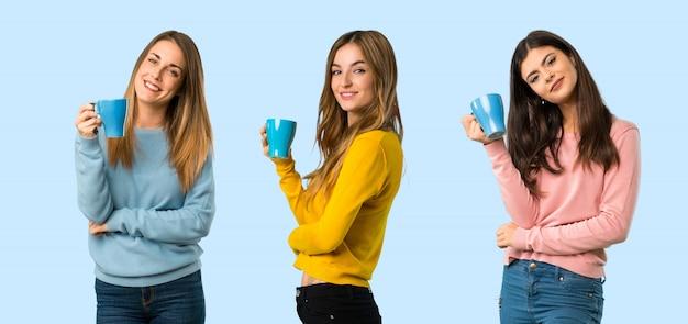 Grupa ludzi z kolorowymi ubraniami trzyma gorącą filiżankę kawy na kolorowym tle