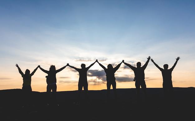 Grupa ludzi z podniesionymi rękami, trzymając się za ręce i patrząc na zachód słońca