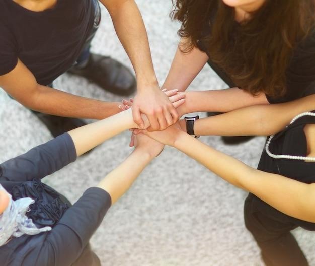 Grupa ludzi z rękami razem pokazując pracę zespołową