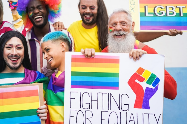 Grupa ludzi z tęczowymi flagami i banerami podczas imprezy gay pride
