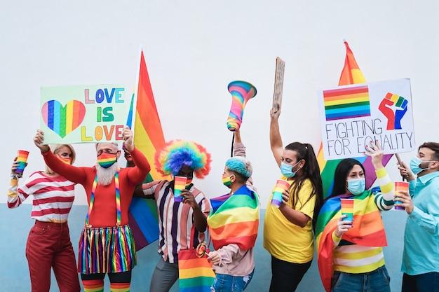 Grupa ludzi z tęczowymi flagami i transparentami tańczy na imprezie gay pride