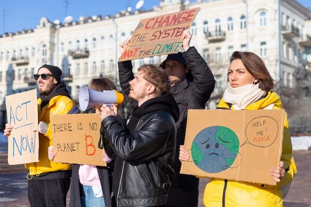 Grupa ludzi z transparentami i megafonem w dłoni protestuje na placu miejskim za czystym światem svae planet.