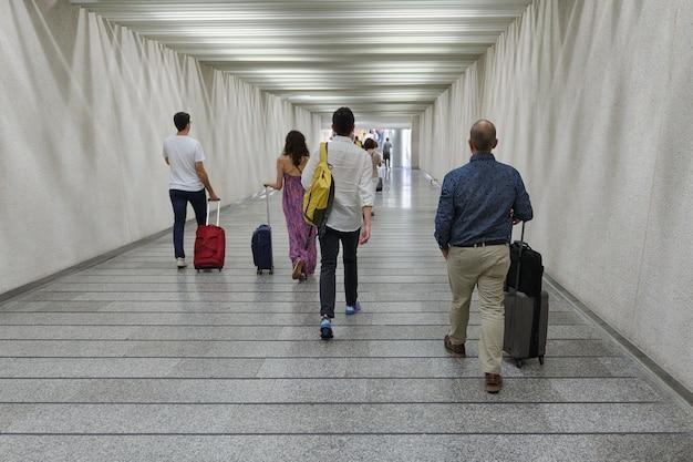 Grupa ludzi z walizkami na kółkach przechodzi przez widok z tyłu przejścia podziemnego