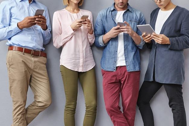 Grupa ludzi ze smartfonami i tabletami
