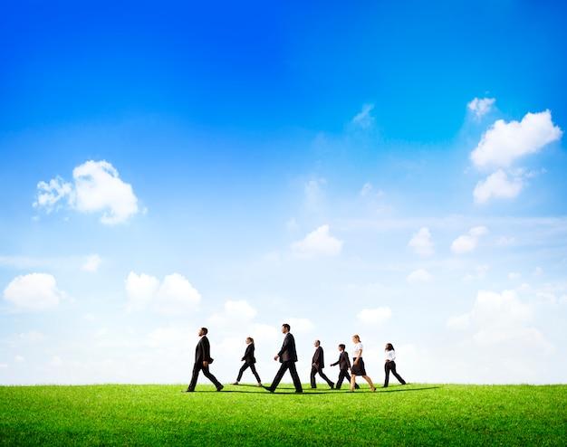 Grupa ludzie biznesu chodzi przez the field w świetle dziennym.