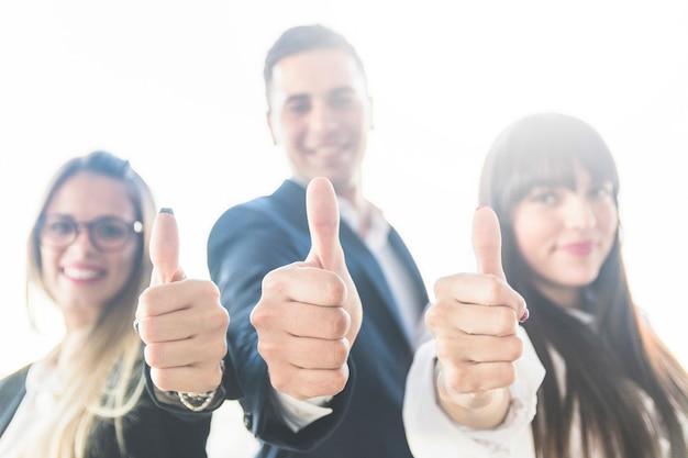 Grupa ludzie biznesu pokazuje kciuk up podpisuje