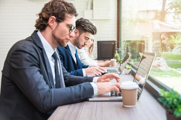 Grupa ludzie biznesu pracuje z nowożytnymi laptopami w biurze