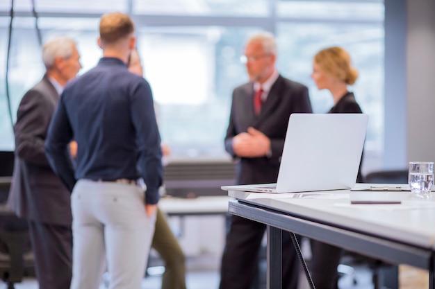Grupa ludzie biznesu stoi przed laptopem na stole