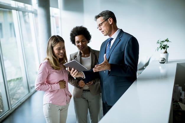 Grupa ludzie biznesu używa cyfrową pastylkę przy spotkaniem w biurze