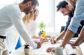 Grupa młodzi biznesmeni analizuje wykres nad drewnianym biurkiem
