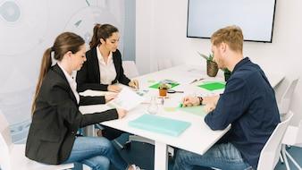 Grupa młodzi biznesmeni pracuje przy miejscem pracy