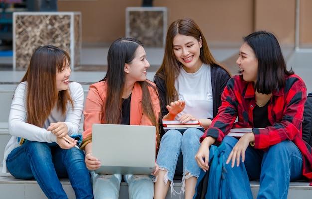 Grupa mądrych azjatyckich studentek z laptopem i notebookami siedzi w kampusie uniwersyteckim i razem prowadzi badania, patrząc na kamery. intymny towarzysz nastolatków na studiach.