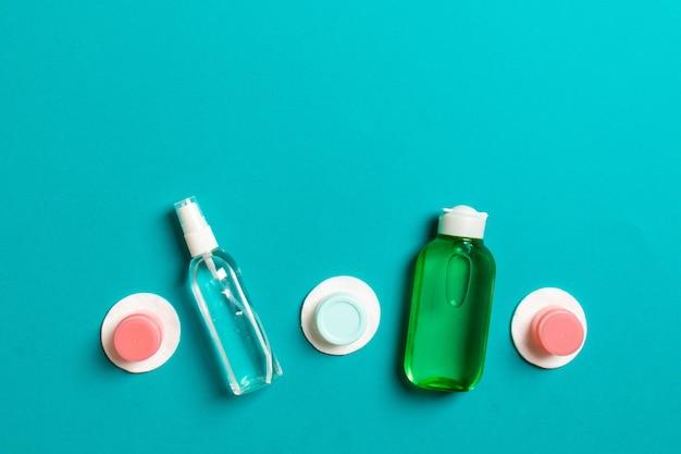 Grupa małych butelek do podróży na kolorowym tle. skopiuj miejsce na swoje pomysły. płaska kompozycja produktów kosmetycznych. widok z góry pojemników na śmietanę z wacikami.