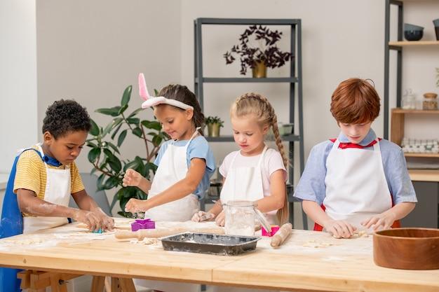 Grupa małych dzieci gotujących ciasteczka na tacy na kuchennym stole pokrytym mąką