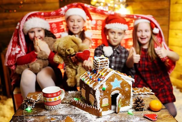 Grupa małych dzieci przyjaciół przedszkolaków w czapkach świętego mikołaja przykryta kocem bawi się zabawkami i robi dom z piernika, świąteczne dekoracje i światła.