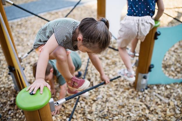 Grupa małych dzieci w wieku przedszkolnym bawiących się na świeżym powietrzu na placu zabaw, wspinających się.