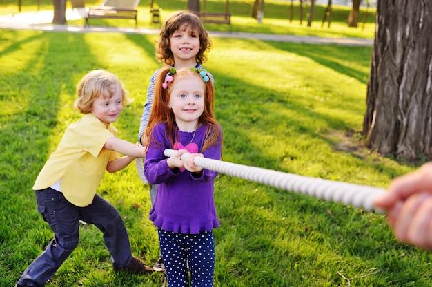 Grupa małych dzieci w wieku przedszkolnym gra w parku przeciąganie liny. gry na świeżym powietrzu, dzieciństwo, przyjaźń, przywództwo, dzień dziecka.