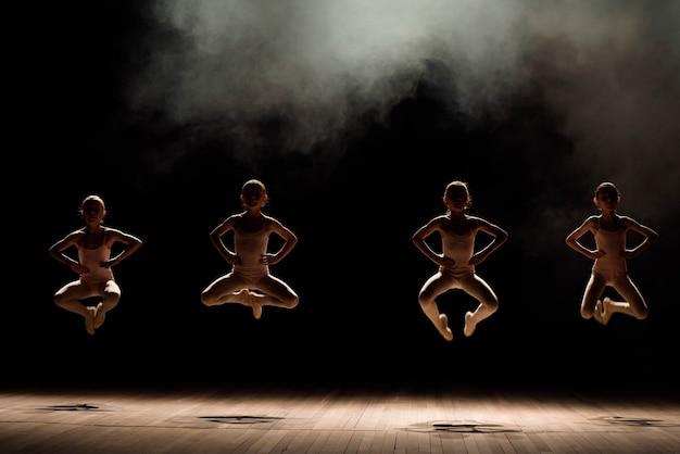 Grupa małych tancerzy baletowych ćwiczy na scenie ze światłem i dymem.