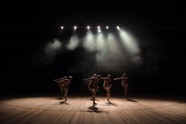 Grupa małych tancerzy baletowych ćwiczy na scenie ze światłem i dymem
