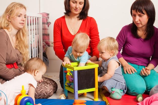 Grupa matek z dziećmi zebrała się, aby porozmawiać i porozumiewać się między dziećmi