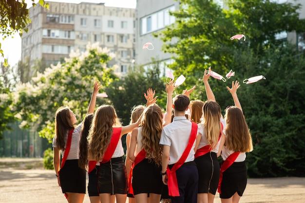 Grupa maturzystów w eleganckich szkolnych mundurkach i czerwonych wstążeczkach z radością rzuca maseczki medyczne jako symbol końca kwarantanny.