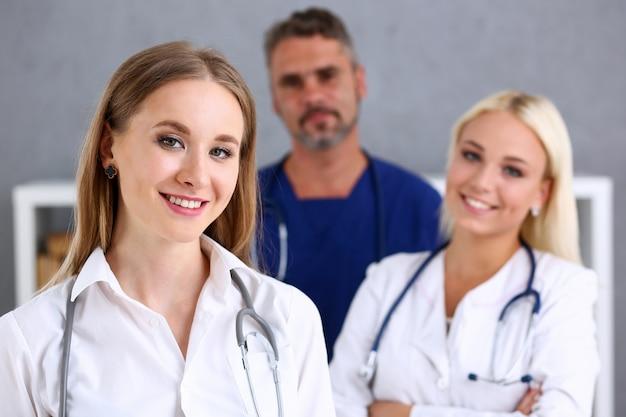 Grupa medyków dumnie pozuje w rzędzie i patrzeje w kamerze