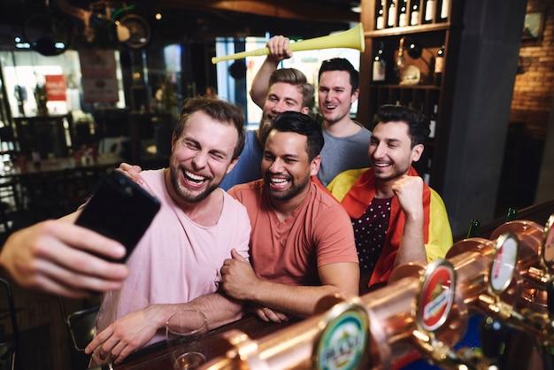 Grupa męskich przyjaciół robi selfie