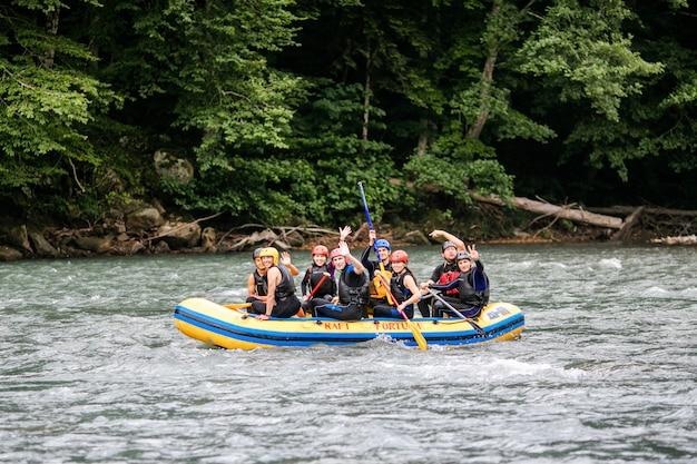 Grupa mężczyzn i kobiet spływa rzeką, uprawia sporty ekstremalne