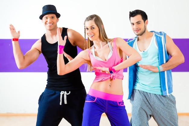 Grupa mężczyzn i kobiet tańczących choreografię fitness zumba w szkole tańca
