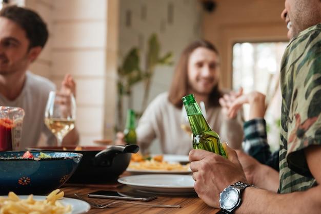 Grupa mężczyzn mówi i pije piwo przy stole