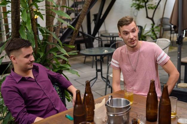 Grupa mężczyzn na zewnątrz siedzi i pije piwo