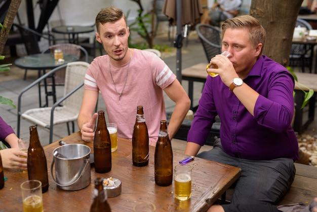 Grupa mężczyzn na zewnątrz siedzi i rozmawia podczas picia piwa