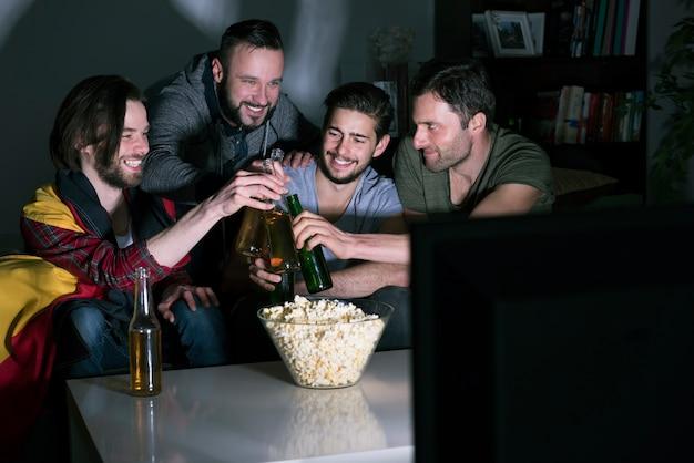 Grupa mężczyzn pije piwo i ogląda piłkę nożną w telewizji