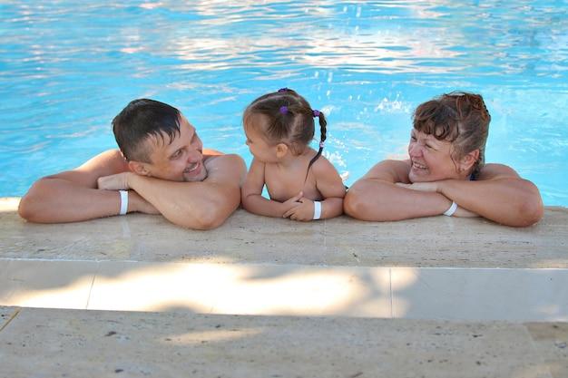 Grupa mężczyzn pływających w basenie. mężczyzna kobieta i dziecko na wakacjach.