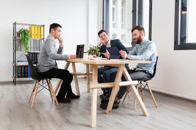 Grupa mężczyzn pracujących razem nad projektem