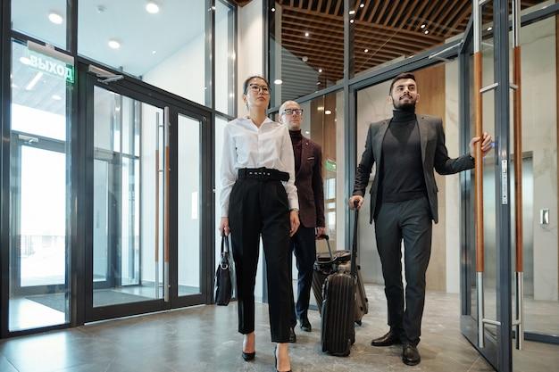 Grupa międzykulturowych podróżujących służbowo z bagażem wjeżdża do hotelowego salonu, aby zamówić pokoje do zamieszkania