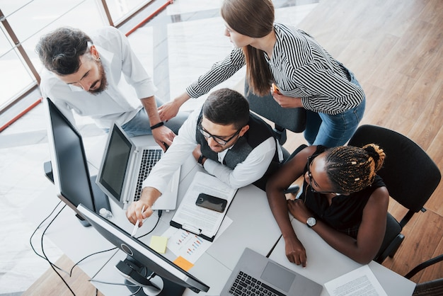 Grupa międzynarodowo zapracowanych osób pracujących w biurze