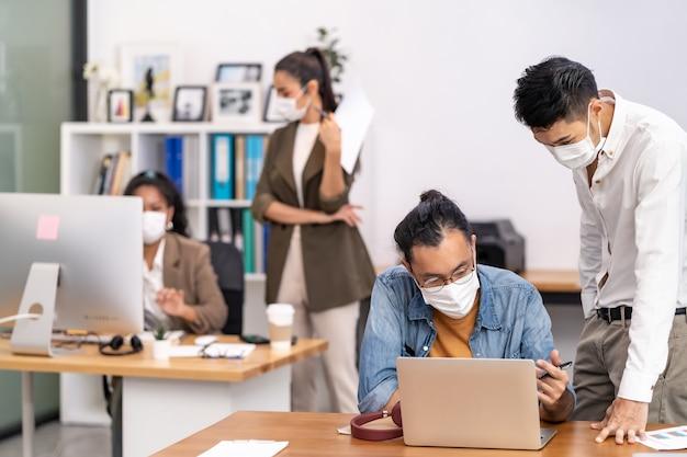 Grupa międzyrasowy zespół pracowników biznesowych nosić maskę ochronną w nowym normalnym biurze