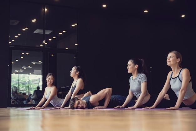 Grupa mieszanej rasy ludzi rasy kaukaskiej i azjatyckiej, zarówno kobiet, jak i mężczyzn ćwiczących jogę w siłowni studyjnej