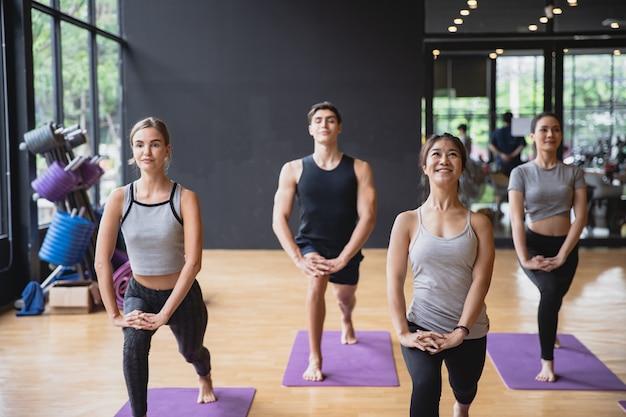 Grupa mieszanej rasy osób praktykujących jogę razem medytujących na rzecz zdrowego stylu życia w klubie fitness