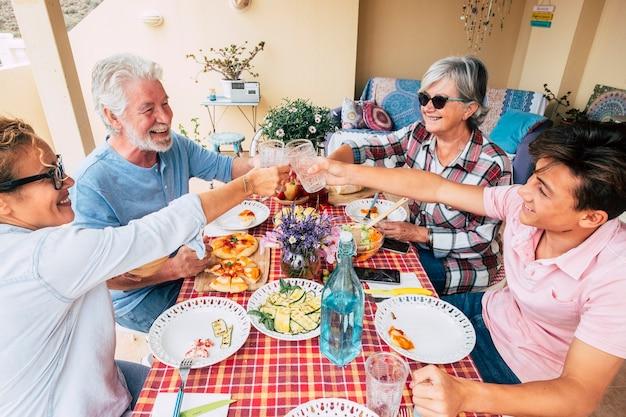 Grupa mieszanych pokoleń ludzi bawi się razem podczas obiadu w domu w plenerze - wesołe kobiety i mężczyźni. od starszego do nastolatka - mama i babcia i syn