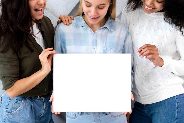 Grupa młode kobiety trzyma pustego znaka