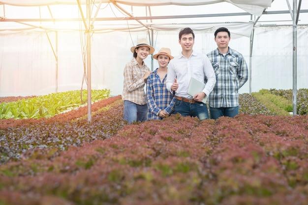 Grupa młodego przedsiębiorcy azjatyckiego biznesowego rolnika mężczyzny i kobiety w hydroponicznej farmie szklarniowej,