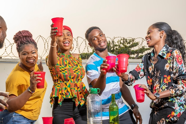 Grupa młodych afrykańskich przyjaciół, którzy spotykają się, wznoszą toast, tańczą i bawią się
