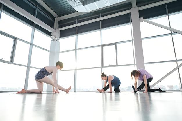 Grupa młodych aktywnych kobiet w odzieży sportowej, trzymając jedno kolano na macie i wyciągając nogi do przodu podczas ćwiczeń jogi na siłowni