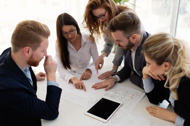 Grupa młodych architektów pracujących razem nad projektem