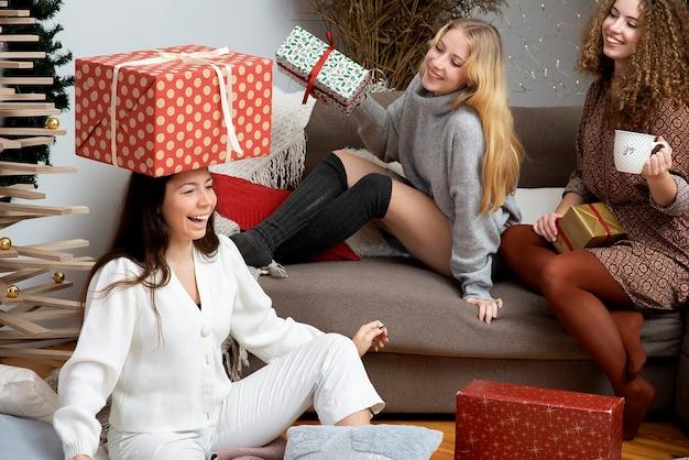 Grupa młodych atrakcyjnych kobiet bawi się pakując świąteczne prezenty w przytulnej domowej atmosferze
